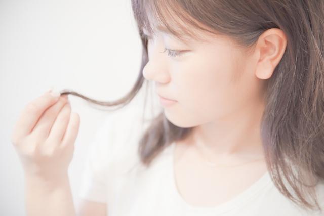 髪の枝毛が気になっている若い女性
